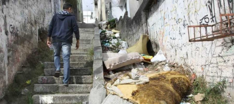 Vão entre escadaria e prédio residencial acumula desde lixo comum até sobras de construção. Foto: Nario Barbosa/DGABC